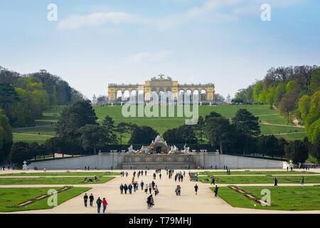 Austria tourism, view of tourists walking through the formal gardens of the Schloss Schönbrunn palace in Vienna, Austria. - Stock Image