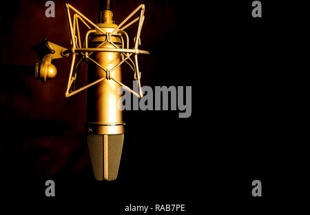 golden color microphone detail in music and sound recording studio, black background, closeup - Stock Image