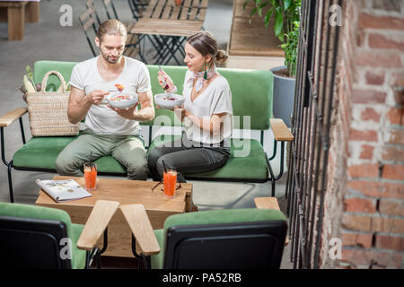 Happy vegetarian couple eating healthy salads sitting together on the sofa at the beautiful green interior. Healthy eating concept - Stock Image