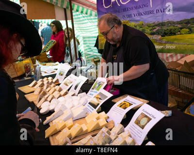 Mr Simon Lacey of Lacey's Cheese offering samples of cheese to customers at Saltburn Farmers Market - Stock Image