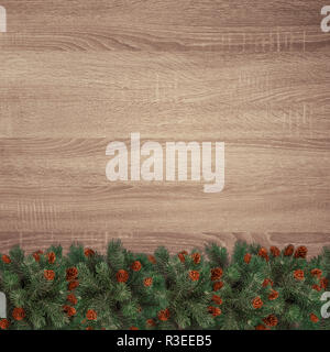 Evergreen fir branches on brown wooden texture background - Stock Image