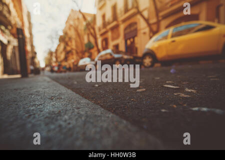 Wide angle view from  asphalt level on narrow street of Barcelona with cars, shallow depth of field, vintage color - Stock Image