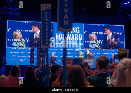 Long Island, USA. 23rd May, 2018. HILLARY CLINTON and Governor ANDREW CUOMO, with a bouquet of flowers for Clinton, are together on stage after Clinton's Keynote Address during Day 1 of New York State Democratic Convention, held at Hofstra University on Long Island. Clinton, the former First Lady and NYS Senator, endorsed the re-election of Gov. A. Cuomo for a third term. Credit: Ann E Parry/Alamy Live News - Stock Image