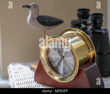 Image of brass clock, bird statue and binoculars. - Stock Image