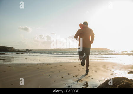 Mature man running on sand, along coastline - Stock Image