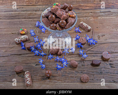 Falling chocolate on a cake stand with flowers - Stock Image