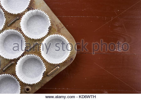 Flat lay above empty white cup cakes papers containers. - Stock Image