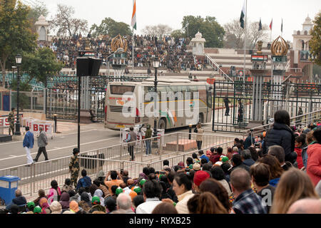 The Attari-Wagah border closing ceremony is interrupted while a bus from Delhi to Lahore crosses the border. - Stock Image