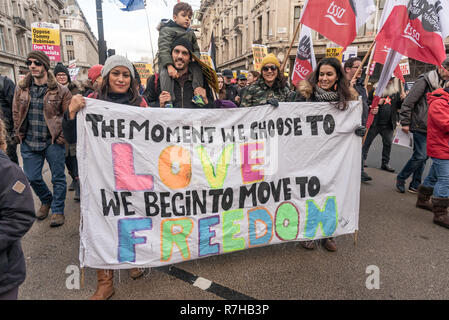 London, UK. 9th Dec, 2018. A group carries a banner 'The Moment we choose to love we begin to move to freedom' in the united counter demonstration by anti-fascists in opposition to Tommy Robinson's fascist pro-Brexit march. The march which included both remain and leave supporting anti-fascists gathered at the BBC to to to a rally at Downing St. Police had issued conditions on both events designed to keep the two groups well apart. Credit: Peter Marshall/Alamy Live News - Stock Image
