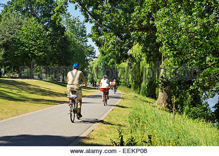 People ride bicycles on a path that runs around the Münstersche Aasee in Münster, Nordrhein-Westfalen, - Stock Image