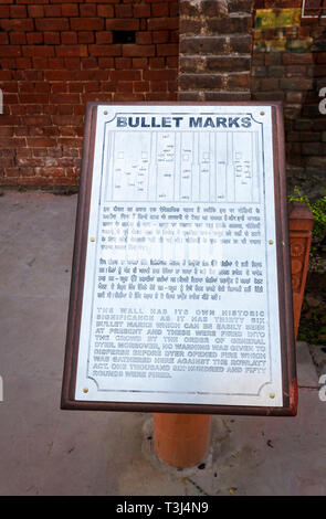 Sign about bullet marks in a brick wall, Jallianwala Bagh, a public garden commemorating the 1919 Jallianwala Bagh shooting Massacre, Amritsar, Punjab, India - Stock Image