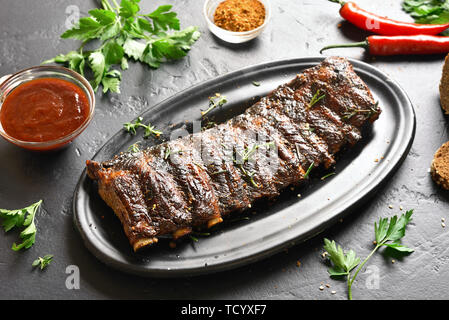 Grilled spare ribs on plate over black stone background. Tasty bbq meat. - Stock Image