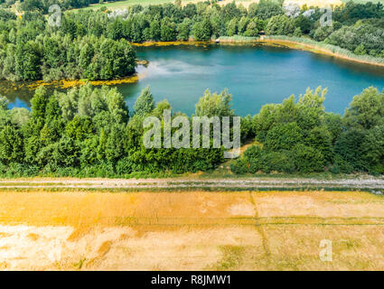 Aerial view with the drone of a blue pond behind a harvested yellow wheat field - Stock Image