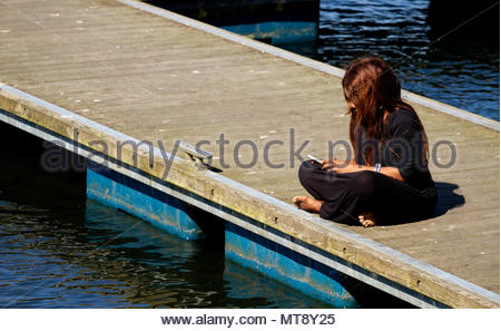 Dundee, Tayside, Scotland, UK. 28th May, 2018. UK weather: Heatwave sweeping across North East Scotland with temperatures reaching 23ºC. A young West African woman with long hair enjoying the glorious sunshine, texting on her iPhone while sitting on the jetty at Clatto Country Park in Dundee, UK. Credits: Dundee Photographics / Alamy Live News - Stock Image