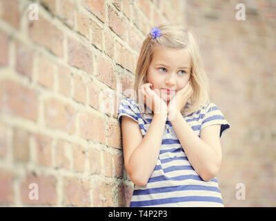 Girl, 10 years, leans against a wall, shy look, Portrait, Germany - Stock Image