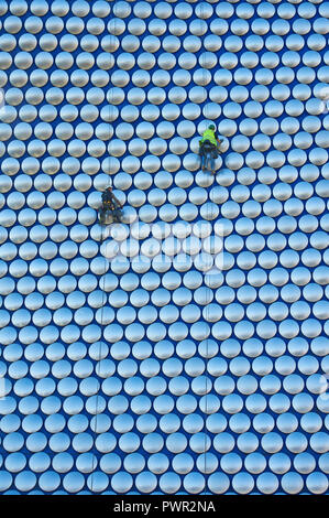 Cleaners suspended by ropes on the outside of Selfridges department store in the Bull Ring, Birmingham - Stock Image
