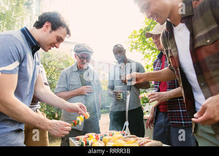 Male friends standing around barbecue grill in backyard - Stock Image