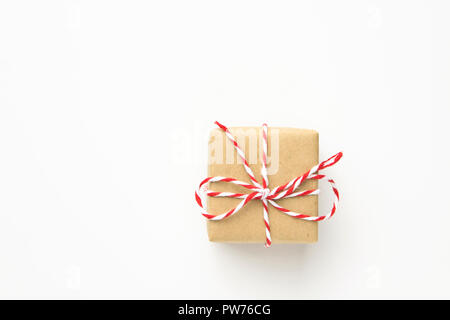 One small gift box wrapped in brown craft paper tied with striped red ribbon on white background. Christmas New Year presents shopping sale poster ban - Stock Image