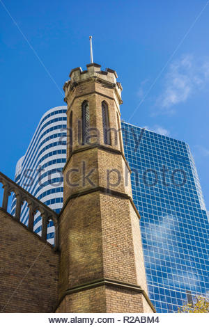 Turret of historic Church of the Holy Trinity Anglican against the modern Eaton Centre in downtown Toronto Ontario Canada - Stock Image