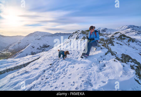 Rest time for a hiker and their dog on Hartsop Above How that leads to Hart Crag in the English Lake District. - Stock Image
