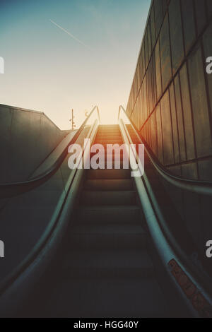 City outdoor grungy modern escalator goes up to sun and teal sky, rusty metal tiled wall on the right, Barcelona, - Stock Image