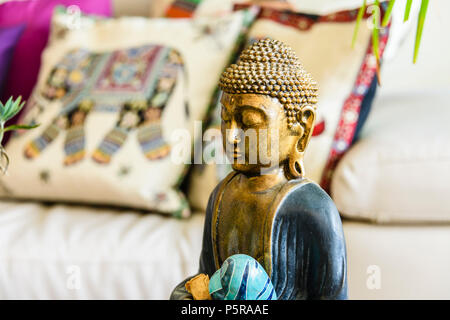 Statue of contemplating Buddha inside a modern, trendy house with eastern interior design influences. - Stock Image