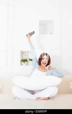 Young woman sitting on the sofa and holding remote control with smile, - Stock Image