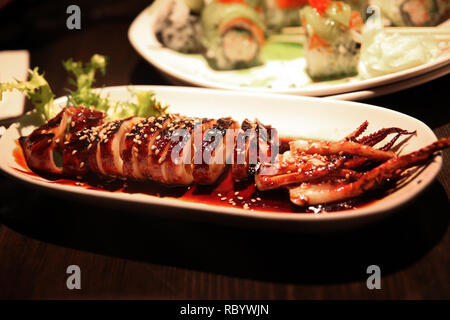 Japanese grilled or barbecued squid with roasted sesame in traditional teriyaki sauce. - Stock Image