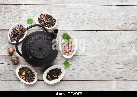 Set of different herbal and fruit dry teas in bowls on wooden table. Top view flat lay with copy space - Stock Image