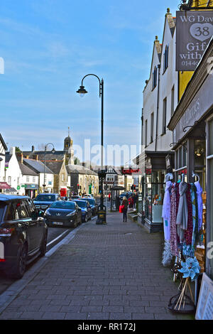 A street view of the High Street in Cowbridge with it's mix of famous brands and small local specialist shops.The old Town Hall is in the background. - Stock Image