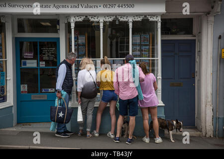 Family looking at properties for sale advertised in an estate agent window in West Dorset, England, United Kingdom - Stock Image