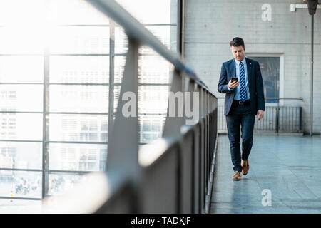 Businessman with cell phone on the move - Stock Image