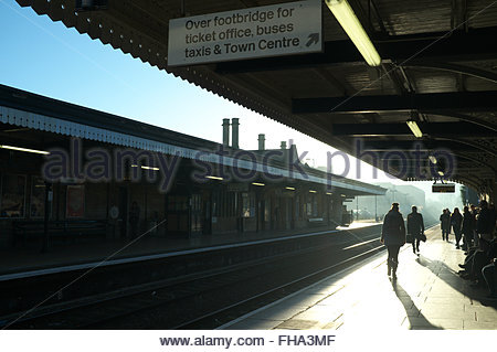 Early morning commuters wait for their train at Stroud railway station in the winter sunshine. Stroud, Gloucestershire, - Stock Image