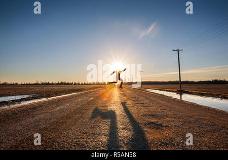 Man skipping over the road with sun covering his head - Stock Image