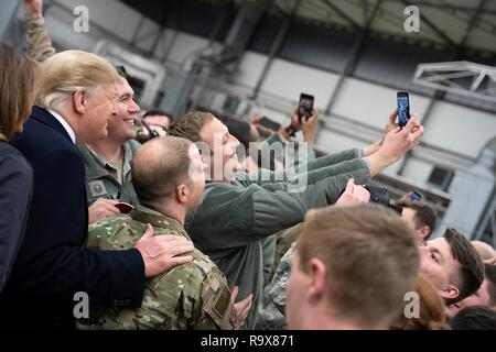 U.S. President Donald Trump takes selfies with U.S. service members during stop-over at Ramstein Air Force Base following a surprise visit to Iraq December 26, 2018 in Ramstein-Miesenbach, Germany. The president and the first lady spent about three hours on Boxing Day at Al Asad, located in western Iraq, their first trip to visit troops overseas since taking office. - Stock Image