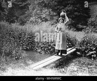 A young countrywoman carries a pot of water on her head over a rustic and rudimentary bridge, 1890s     Date: 1890s - Stock Image