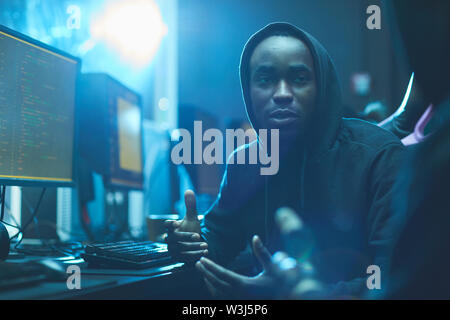 Content creative young Afro-American coding specialist in hoodie gesturing hands while discussing web script with colleague - Stock Image