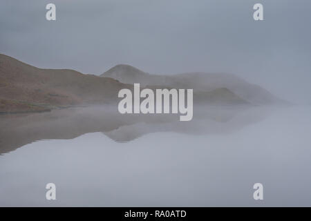 Misty reflections in Easedale Tarn, Grasmere, Lake District, Cumbria - Stock Image