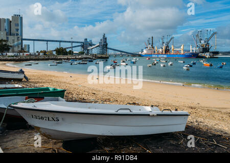 Trafaria, Portugal - Dec 16, 2018: Beach next to a deep water terminal and silo for grain, derived products and oleaginous products in Trafaria, Portu - Stock Image