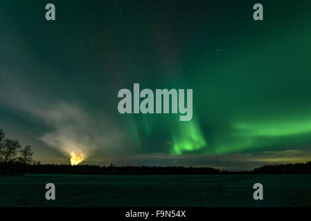 Green northern lights and smokestack of factory. - Stock Image