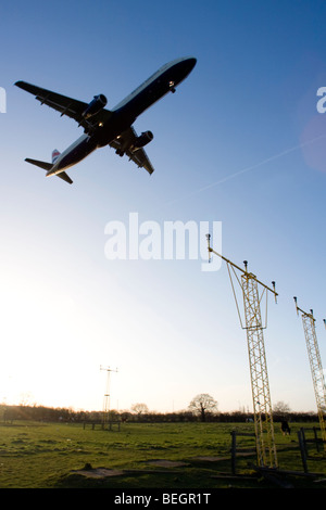 Low angle view of commercial aircraft flying over approach lights. - Stock Image