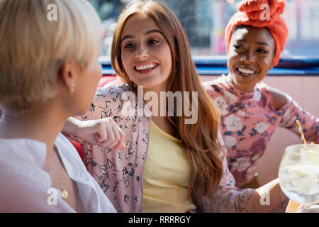 Young women friends talking in restaurant - Stock Image