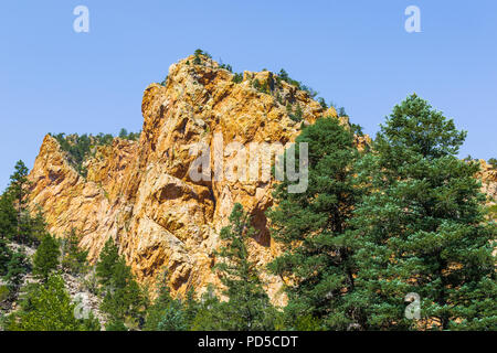 A closeup of a craggy peak in the southwest mountains, with green-leafed trees and blue sky.   Good for background. - Stock Image