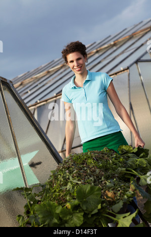 portrait of young woman working in nursery - Stock Image