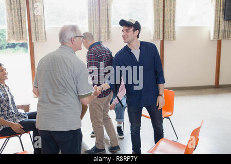 Men shaking hands in group therapy - Stock Image