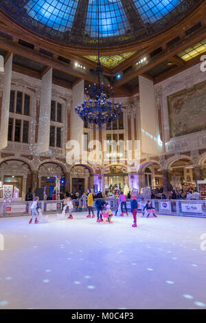 Children are skating on the ice rink inside the Chamber of Commerce in Lille, France - Stock Image