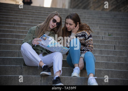 Two young women sitting on stairs and looking at the map. Mid shot - Stock Image