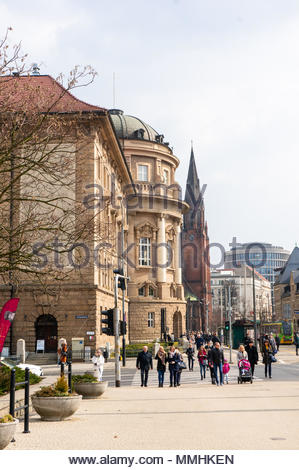 People walking on a zebra crossing with the medical sciences university building in the background on the Fredry street in Poznan, Poland - Stock Image