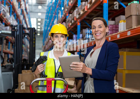 Warehouse manager and female worker smiling while holding digital tablet - Stock Image