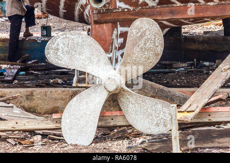 Ships propeller on fishing boat in dry dock for repairs, Sichon, Thailand - Stock Image